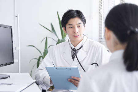 Japanese male doctor examining female company employees