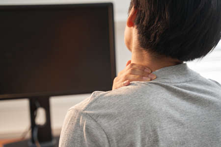 Japanese male businessman who has a pain in his neck from work from home