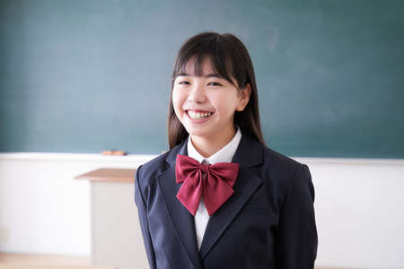 Japanese girl junior high school student standing with a smile in the classroom