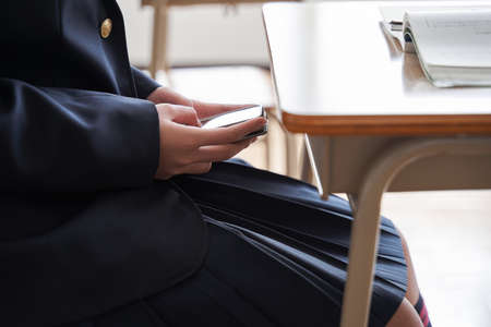 Japanese girl junior high school student who hides and operates a smartphone in the classroom