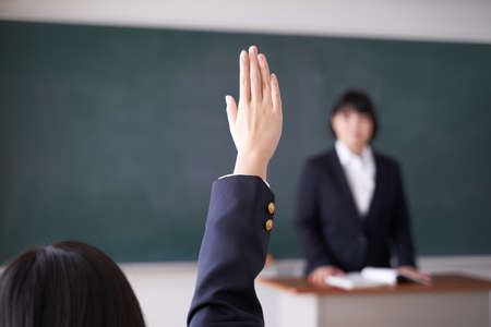 Japanese female junior high school student raises hand in the classroom