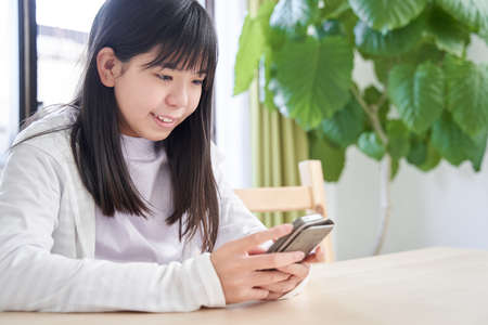 Japanese girl junior high school student who sees a smartphone in the living room