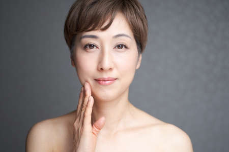 A middle-old Japanese woman smiling from the camera's point of view while holding the corners of her mouth Stock Photo