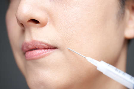 Middle-old Japanese woman hitting cosmetic injections
