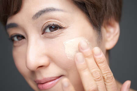 Middle-old Japanese woman applying foundation to cheeks Banco de Imagens