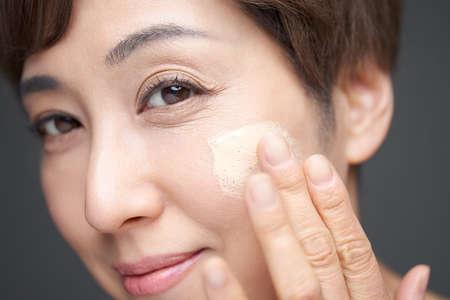 Middle-old Japanese woman applying foundation to cheeks 版權商用圖片