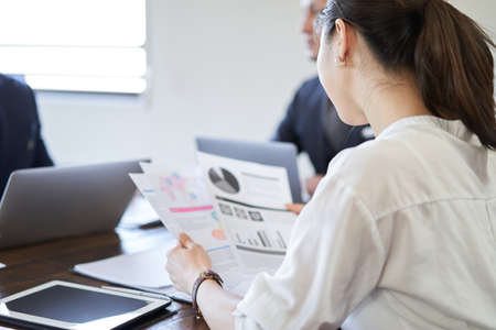Asian female businesswoman looking at material