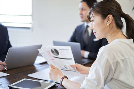 Japanese female businesswoman looking at conference materials