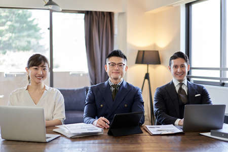 Asian and Latin business person smiling from camera's point of view 版權商用圖片
