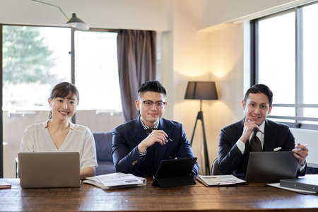 Asian and Latin business person smiling from camera's point of view Banco de Imagens