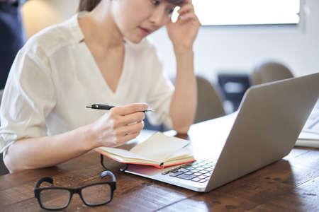 Asian woman worried about deadlines for pc work Banco de Imagens