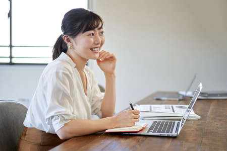 Asian woman working with a smile on her face with telework