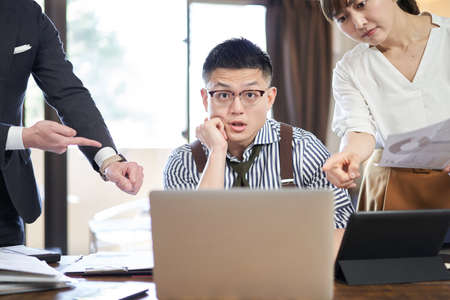Asian male businessman surprised by work volume and deadline