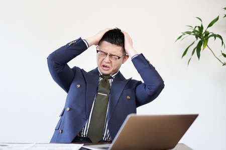 Asian businessman holding his head at work