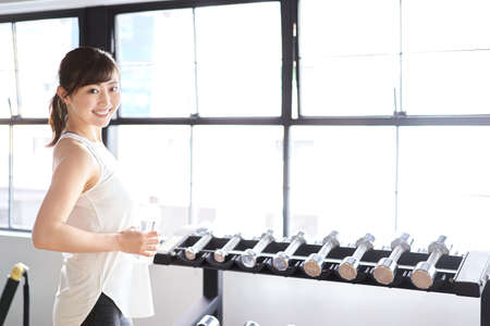 Asian woman with a smile and dumbbell training