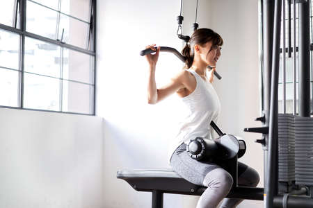 Asian woman back rat pull-down at training gym