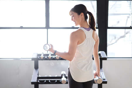 Asian woman with dumbbell at training gym
