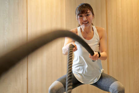 Asian woman on battle ropes at training gym