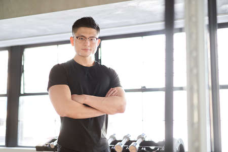 Asian male trainer with arm folds from the camera's point of view