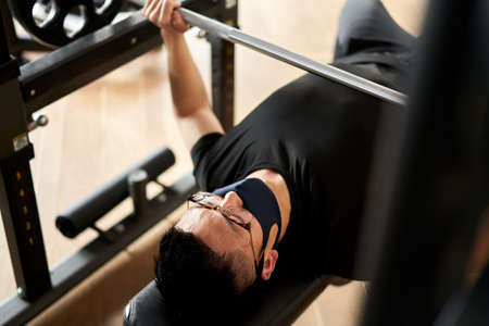 Asian man bench-pressed with mask on