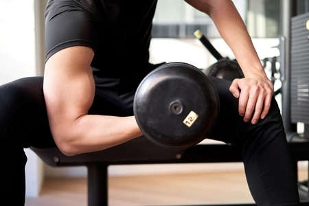 Asian man in dumbbell curls at training gym