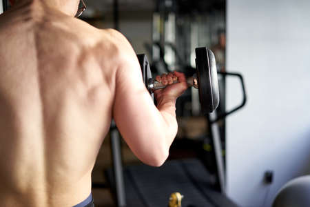 Asian man lifting dumbbell in back
