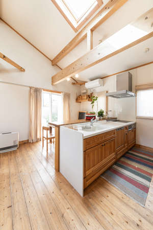 A kitchen in a house with sunlight from the skylight