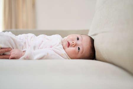 Asian baby lying on sofa