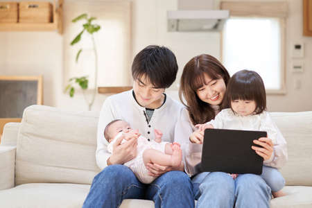 Asian family sitting on sofa looking at tablet