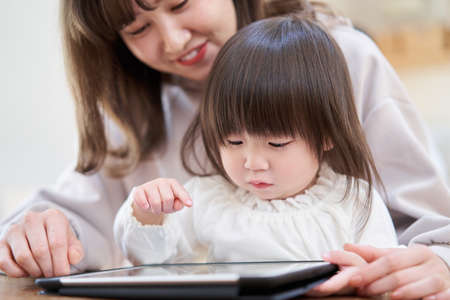 Asian girl looking at tablet with mom Reklamní fotografie