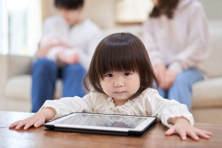 Asian girl looking at tablet by her person