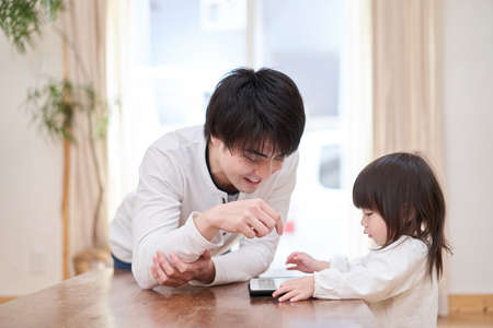 Asian girl looking at tablet with daddy