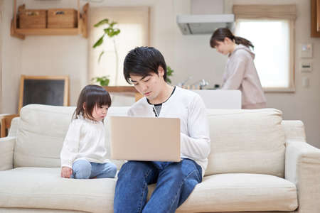 Asian dad taking care of kids as mom does housework