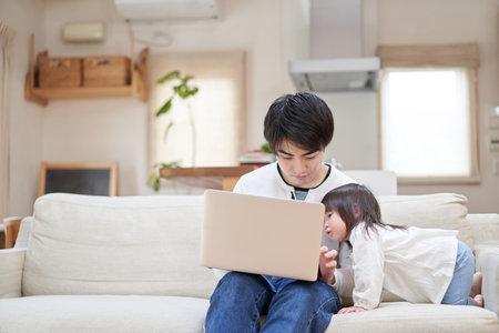 Asian child interrupting daddy during telework