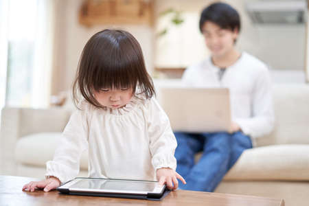 Dad working from home and Asian child looking at tablet by him