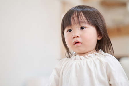 Asian toddler chasing mom with anxious look
