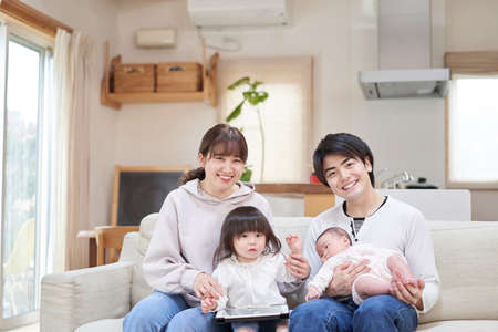 Asian family sitting on sofa from camera's point of view Reklamní fotografie