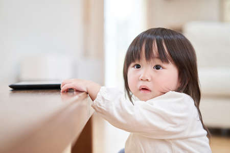 Asian toddler looking into the distance with an anxious expression