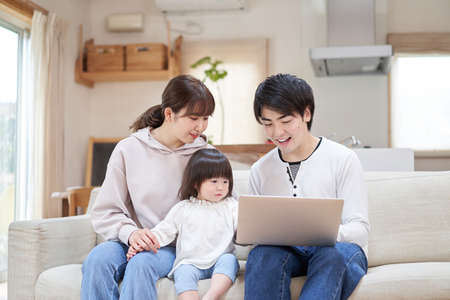 Asian family looking at computer in living room