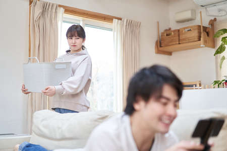 Asian husband playing games with wife doing housework