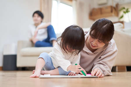 Mother and child painting and relaxing daddy