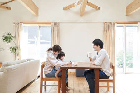Asian family relaxing in living room in one house