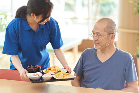 a caregiver who serves meals to the elderly