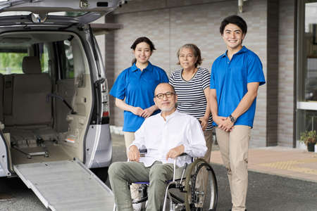 Wheelchair riding elderly and caregivers Banque d'images