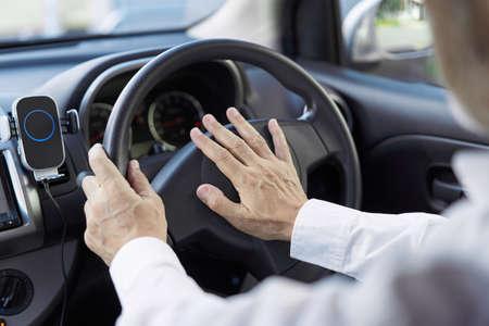 Back view of an elderly person honking a car horn Standard-Bild