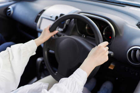 Hands of a woman driving a car