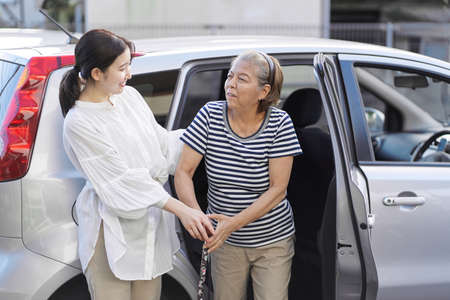 A woman who removes an elderly person from a car Standard-Bild