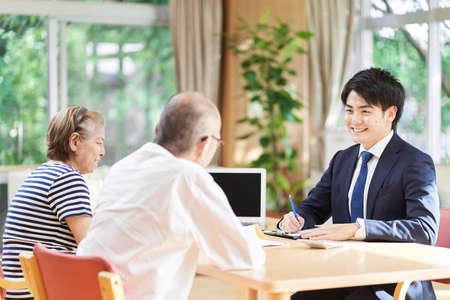 A businessman who advises an elderly couple on a long-term care facility Standard-Bild