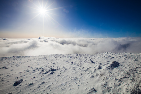 Alpine view of snow, sun and clouds