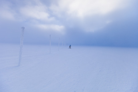 Cross country skier skiing in windy weather photo